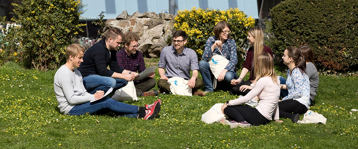 Students gathered in the grass with several European Campus bags.